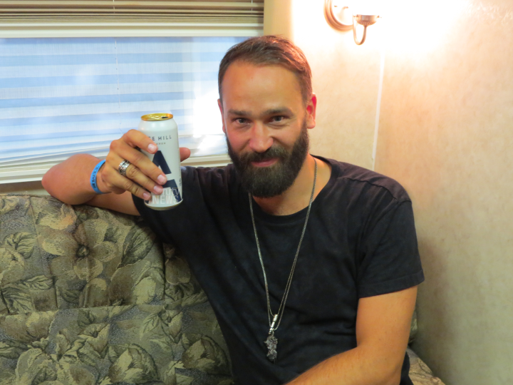 Jonas Rathsman poses with his Ace Hill beer can in his trailer backstage at TIME Festival. (Photo credit: Codi-Lyn Dunkley/RUtv News)