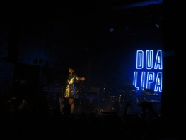 Dua Lipa performed in front of a neon sign with her name on it. (Photo credit: Angela McLean/RUtv News)