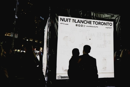 In Nathan Phillips Square, a couple stops to read a map of the Nuit Blanche installations. (Photo credit: Emma Sandri/RUtv News)