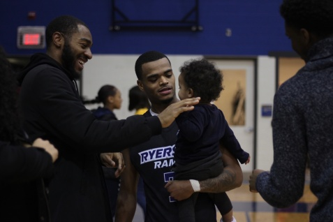 Myles Charvis spends some family time and has a moment with fromer Ryerson Basketballer and current Raptors 905 member Aaron Best following the loss against the Ravens (Photo credit: Brent Smyth/RUtv News).